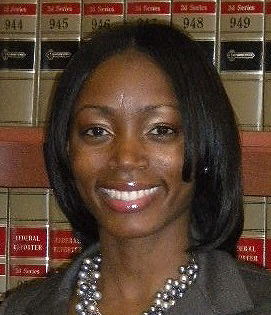 Keshara Davis headshot of a young smiling African American woman, she has medium length black has and is wearing a dark grey blazer and a pearl statement necklace