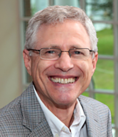Larry Krieger for the College of Law headshot of an older smiling Caucasian man with grey hair wearing glasses, a grey striped sportcoat and a white shirt