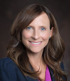 Margaret Good headshot of a middle aged smiling Caucasian woman with brown hair and blue eyes wearing a pink blouse and a navy blue blazer