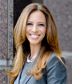 Michelle Suskauer headshot of young Caucasian woman in a grey business suit in a pearl necklace. She has long straightened brown hair and is smiling.
