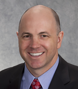 Damian C. Taylor headshot of a middle aged smiling Caucasian man wearing a black suit with a blue shirt and red tie.