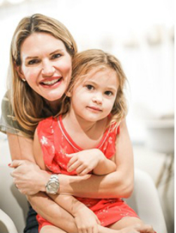 Deborah Baker-Egozi a smiling Caucasian woman with a young girl with light brown hair sitting in her lap