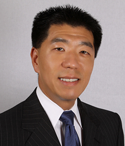 Jay Kim headshot of a smiling Asian man in a black suit with a white shirt wearing a dark blue tie