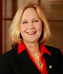 Julia Frey headshot of a Caucasian woman with medium length blonde hair wearing a bright red shirt, black blazer and a heart necklace. She has a warm happy smile and is wearing red lipstick.