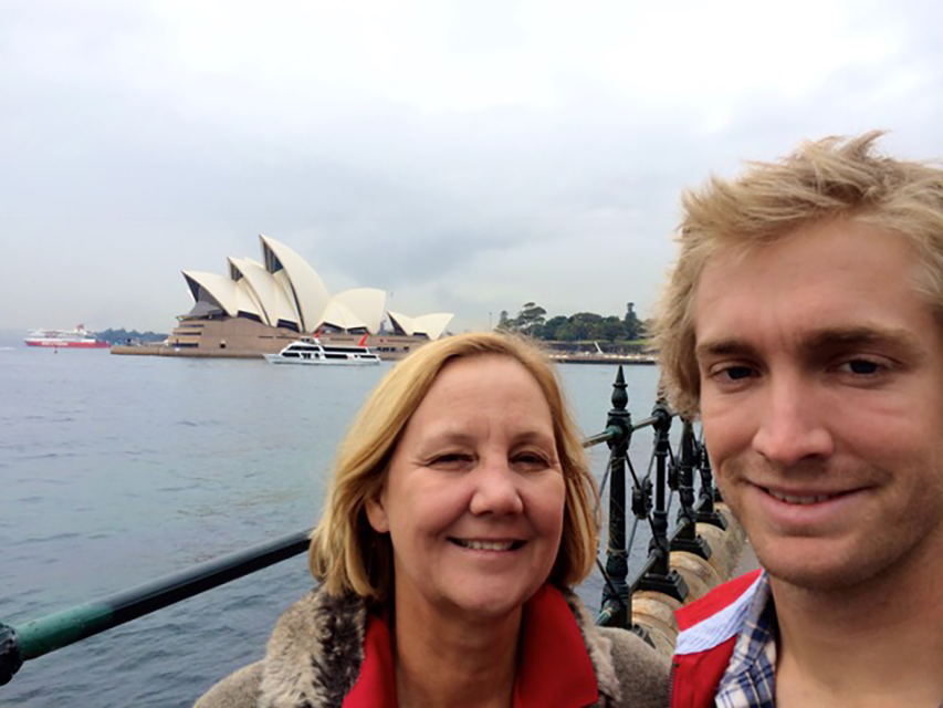 Julia Frey a Caucasian woman in a coat with a fur collar standing in front of Sydney opera house with a young blonde Caucasian man who is smiling.