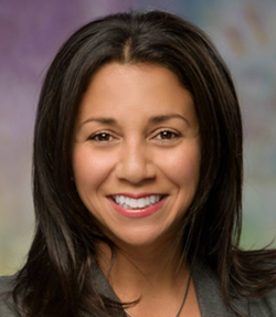 Michelle Bedoya Barnett headshot of a happy Latina woman with medium length dark hair. She has brown eyes and is wearing a grey top.