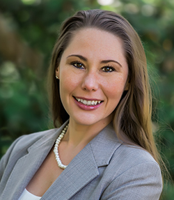 Stephanie Hayes headshot of a smiling Caucasian woman in a grey blazer and white shirt. She is wearing a pearl necklace, has brown eyes and long brown hair. There are trees in the background.
