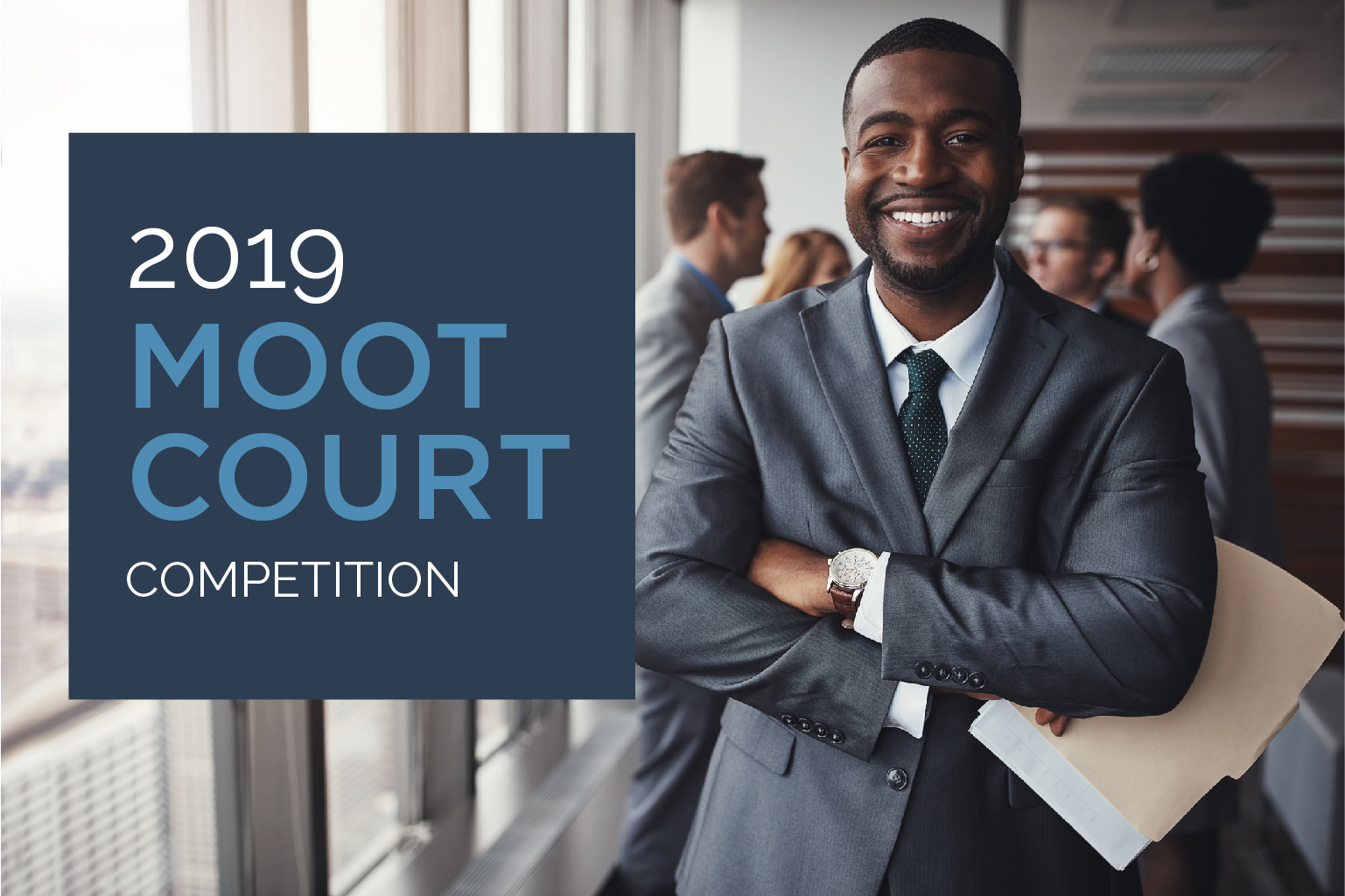 FLAYLD 2019 Moot Court Competition with young male lawyer in grey suit smiling at camera in office