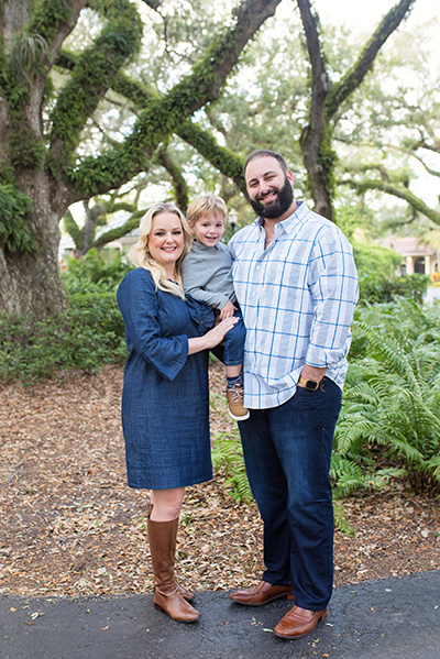 Casseland Cassel a Caucasian woman with blonde hair wearing a blue with her Caucasian husband who has a black beard and black hair and their young blonde son