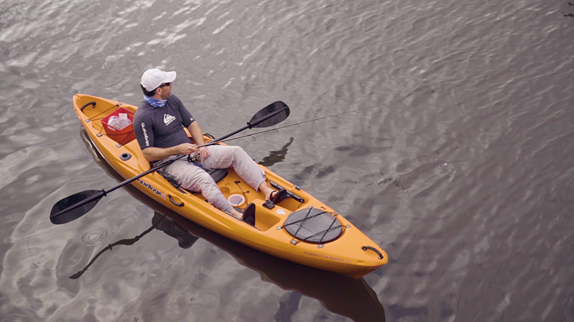 Ron Ponzoli a Caucasian man in a blue shirt, flip flops and a white hat sitting in orange kayak on water