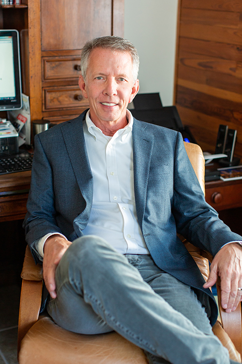 Wayne LaRue Smith an older Caucasian man with a grey sport coat and white shirt and jeans sitting in office chair smiling at camera