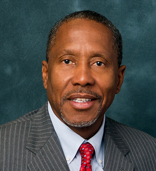 Darryl Rouson headshot, older African American man with brown eyes wearing gray suit and red tie and a gold lapel pin.
