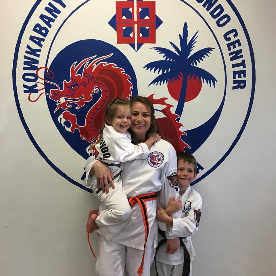 Traci Koster in Taekwondo, a young Caucasian woman with two young Caucasian children, one is a boy and one is a girl, standing behind an Tae Kwon Do background with a dragon and tree symbol