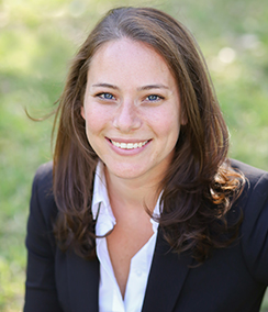 Traci Koster headshot, a young Caucasian woman with blue eyes and long brown hair wearing a white shirt and black blazer with a green grass background