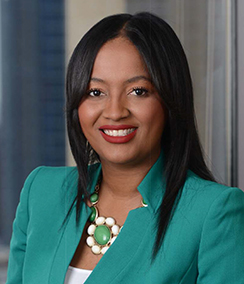 Alison Smith headshot African American woman in a teal blazer and white shirt in front of office window, she is smiling and wearing lipstick, and has long black hair.