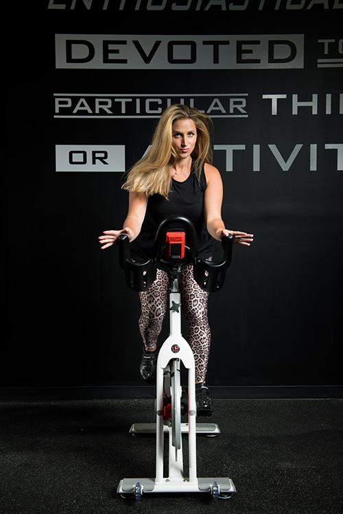 Emily Romano a young Caucasian woman in workout clothing including a black top and cheetah print leggings riding a fitness bike with a black background