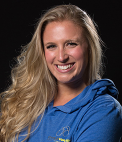 Emily Romano headshot, a young Caucasian woman with long blonde hair wearing a blue activewear shirt with a hood