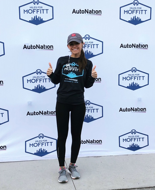 Melina Garcia, a young Latina woman in a grey hat, sneakers and running gear standing in front of event backdrop