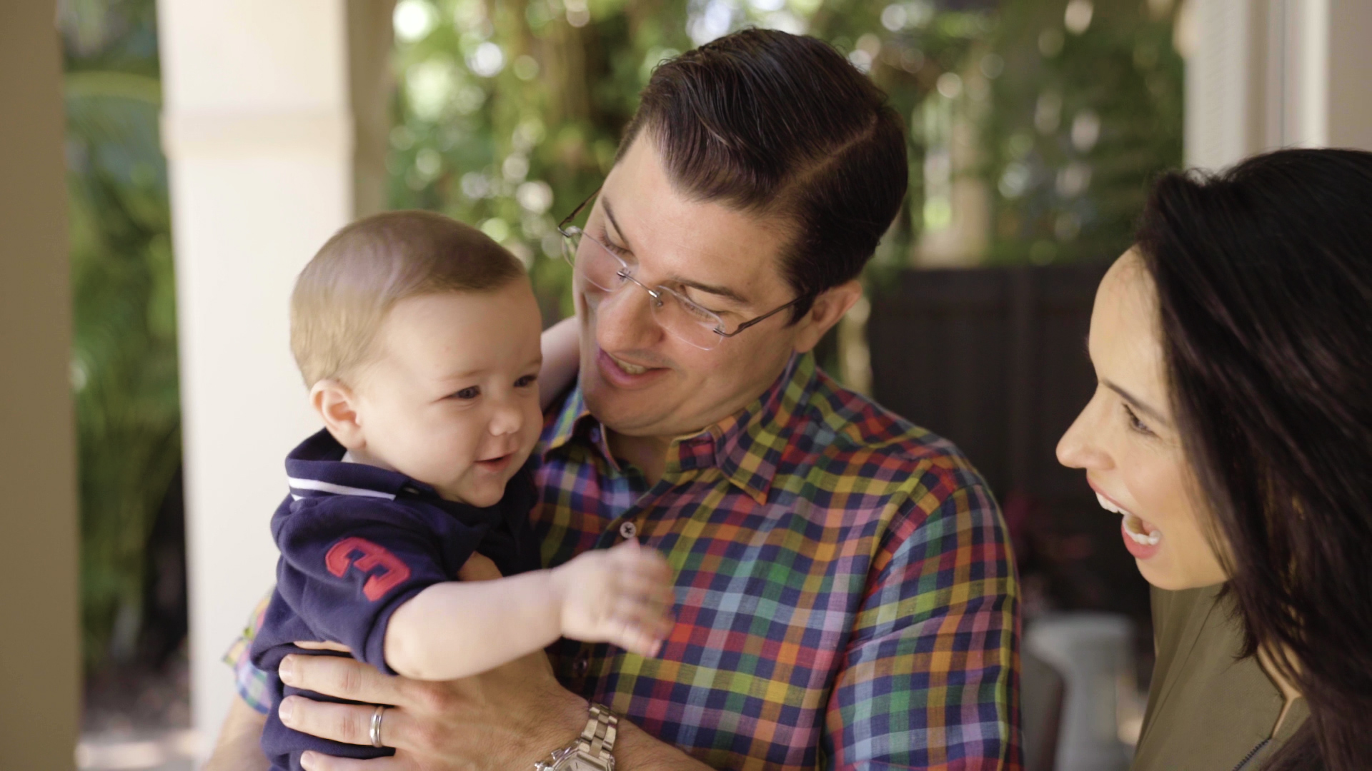 Latino man in glasses and multi colored shirt holding a small infant boy in a blue shirt with a caucasian woman with long brown hair smiling, on a patio outside and sun shining, greenery in background