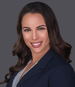 Niki Martell headshot caucasian woman in a dark blue blazer and light blouse with a grey background, long brown hair, brown eyes, smiling