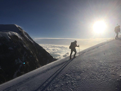 Image of Two Men climbing a tall snowy mountain with clouds and sun in the background