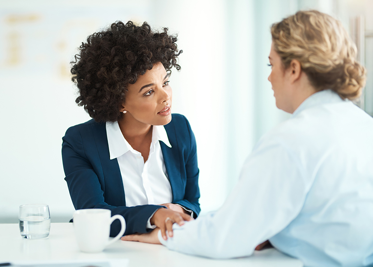 Shot of two businesspeople having a discussion in a modern office, African American woman in a blue sweater with white shirt and pearl earrings and curly hair comforting a caucasian woman with blonde curly hair in a bun wearing a light colored shirt