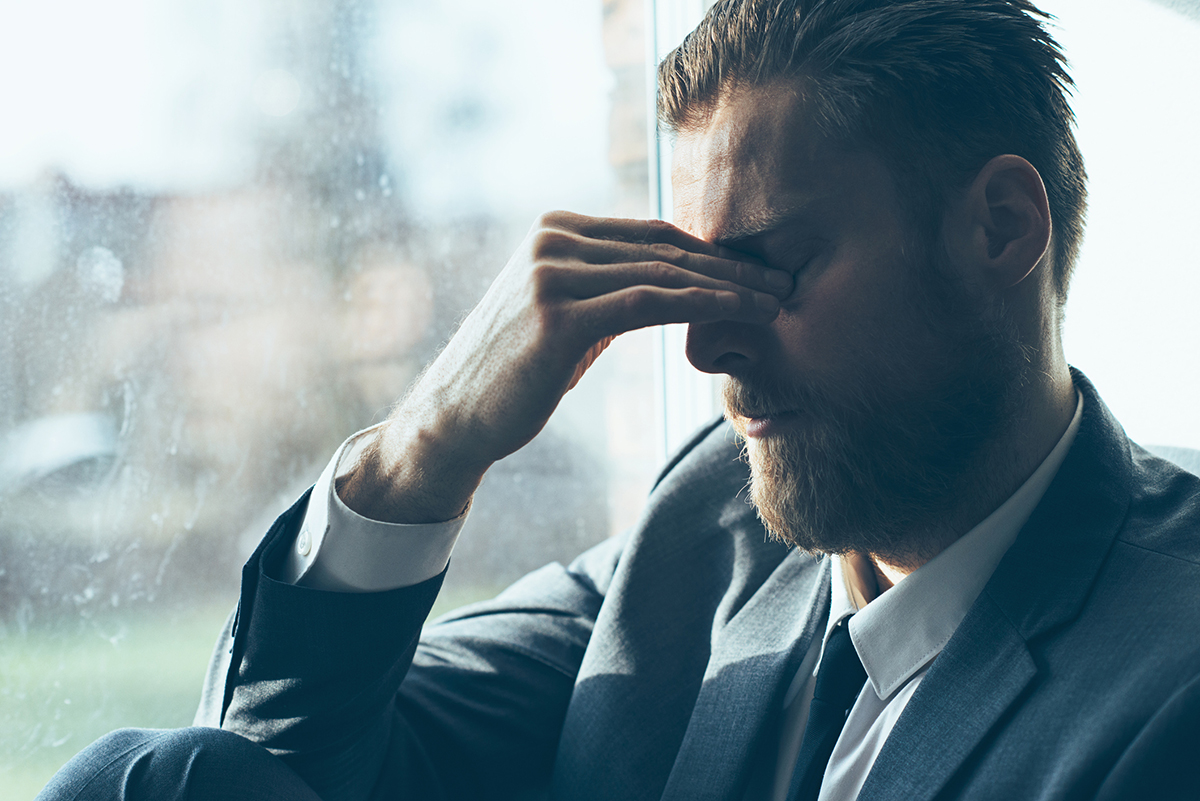 Caucasian Man in a suit suffers from fatigue and perhaps insomnia, He is tired and stressed out. He takes a break and covers his eyes.
