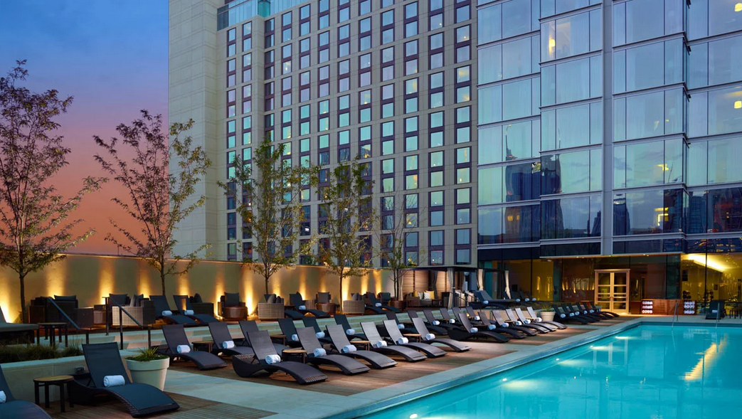 Omni Hotel Nashville, photo taken at twilight, large mirrored building with pool and lounge chairs