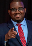 Brandon Sapp headshot, African American Man in a dark suit, blue shirt and red tie, smiling and pointing at camera, black glasses