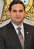 Jose C. Campa headshot, Latino Man in a black suit with a burgundy tie and lapel pin, brown eyes, black hair