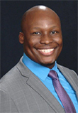 Masimba M. Mutamba headshot, African American man in a grey suit with blue shirt and blue tie, smiling, brown eyes, bald